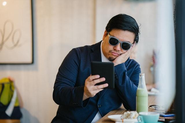 Znudený muž v slenčných okuliaroch a modrom obleku pozerá do tabletu.jpg