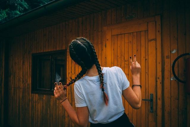 Žena so zapletenými vrkočmi stojí pred nízko podlažným domčekom