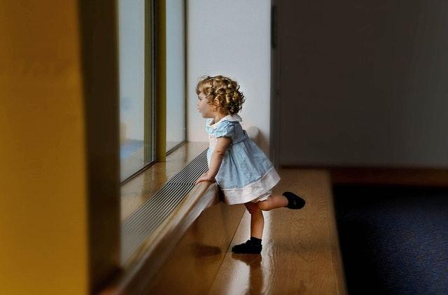 Dievčatko v modrých šatách stojí pri veľkom okne