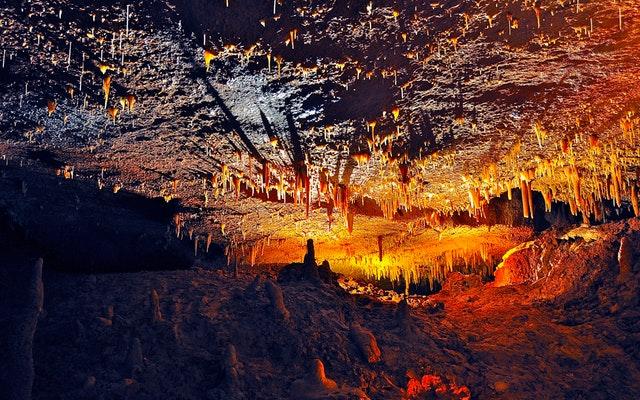 Jaskyňa nasvietená na červeno a oranžovo s kvapľami