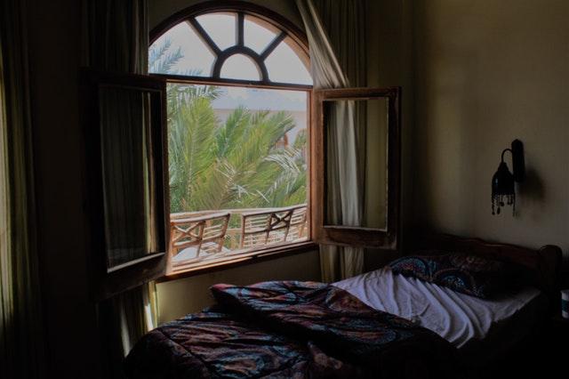 Posteľ s farebnými obliečkami pod oknom s drevenými okenicami
