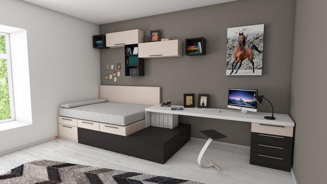 Malá miestnosť s posteľou, pod ktorou sú šuplíky