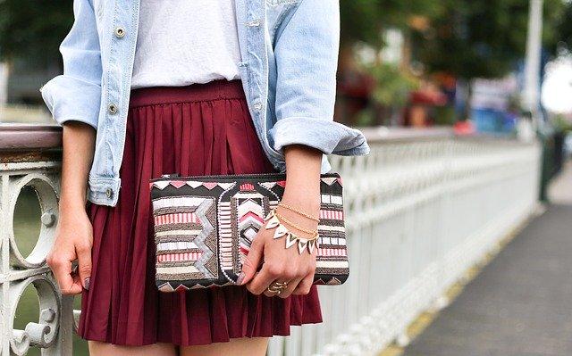 Žena v sukni drží v ruke farebnú kabelku a na ruke má niekoľko náramkov a retiazok.jpg