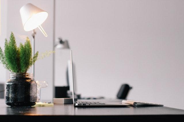 Čierny pracovný stôl s počítačom, rastlinou a stolovou lampou.jpg