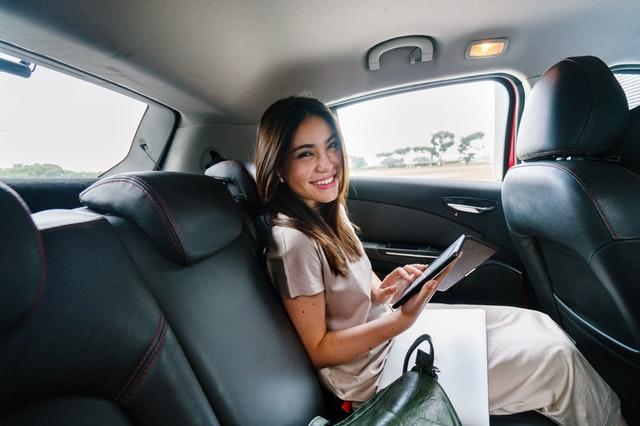 Žena v dlhých bielych šatách sedí v aute a usmieva sa.jpg