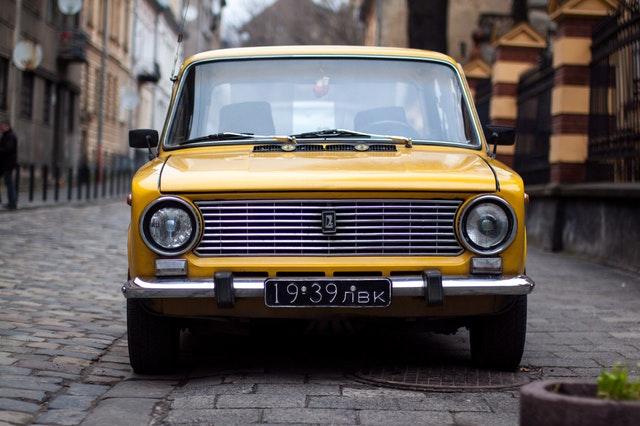 Žlté auto zaparkované v meste na zámkovej dlažbe.jpg